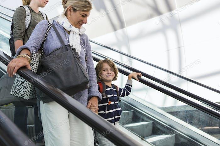 Lächelnder 5-jähriger Junge, der mit seiner Mutter und einer älteren Schwester auf dem Flughafen unterwegs ist