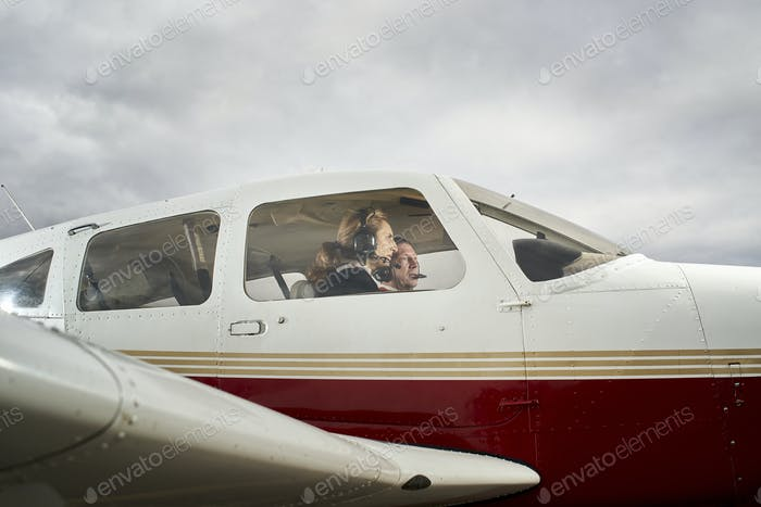 Plane in flight. Female flight instructor giving flight lessons to a student.