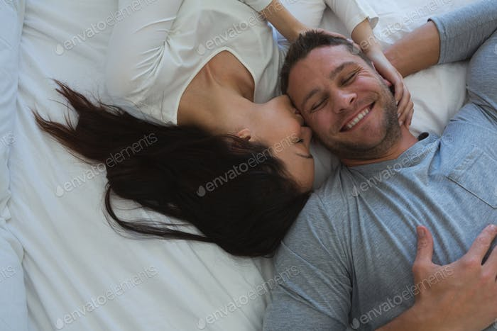 Couple lying on bed in bedroom at home