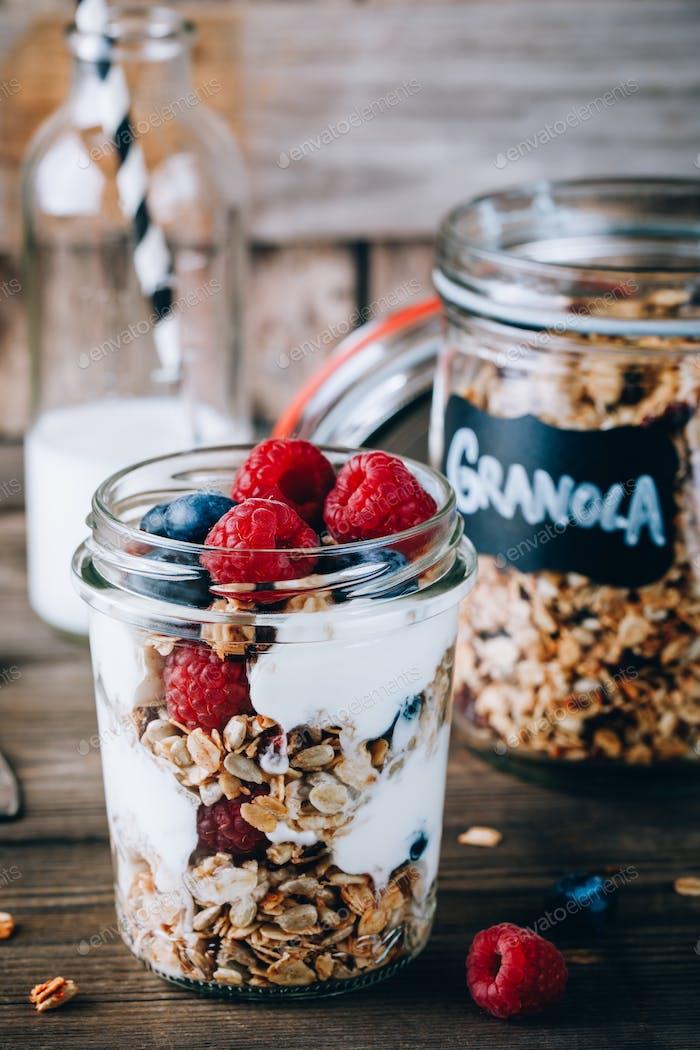 Gesundes Heidelbeer- und Himbeerparfait mit griechischem Joghurt im Glasmalerglas auf Holzhintergrund