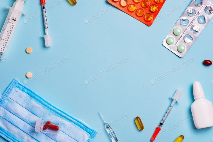 Syringes, pills and medical blue shielding bandage on a blue background with copy space