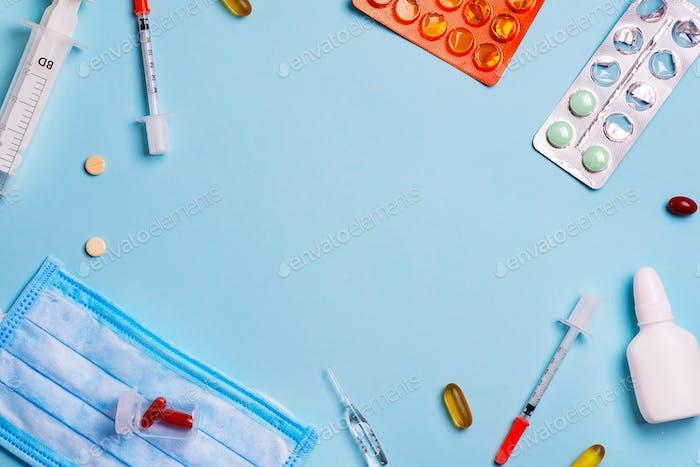 Spritzen, Pillen und medizinische blaue Abschirmbandage auf blauem Hintergrund mit Kopierraum