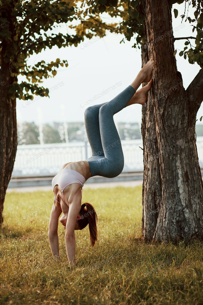 Spending summertime weekends usefully. Young woman with slim type of body does exercises in the park