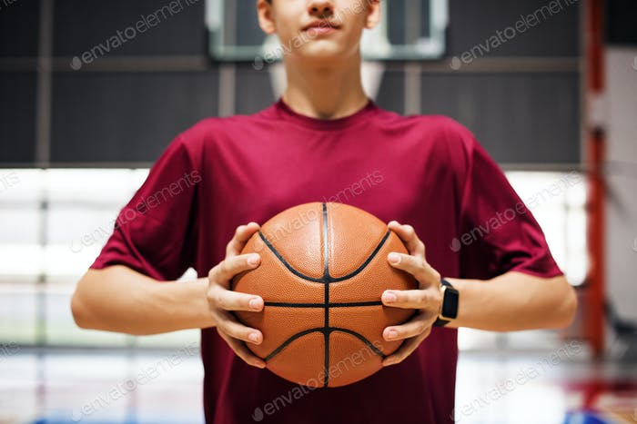 Thumbnail for Teenage boy holding a basketball on the court