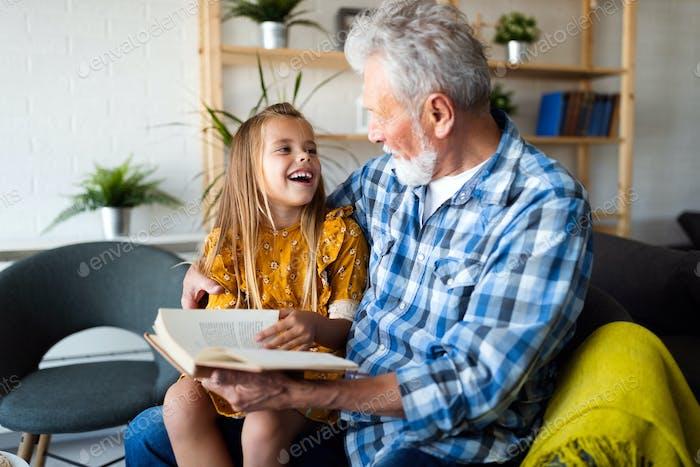 Glückliches kleines Mädchen mit Großvater lesen Geschichte Buch zu Hause