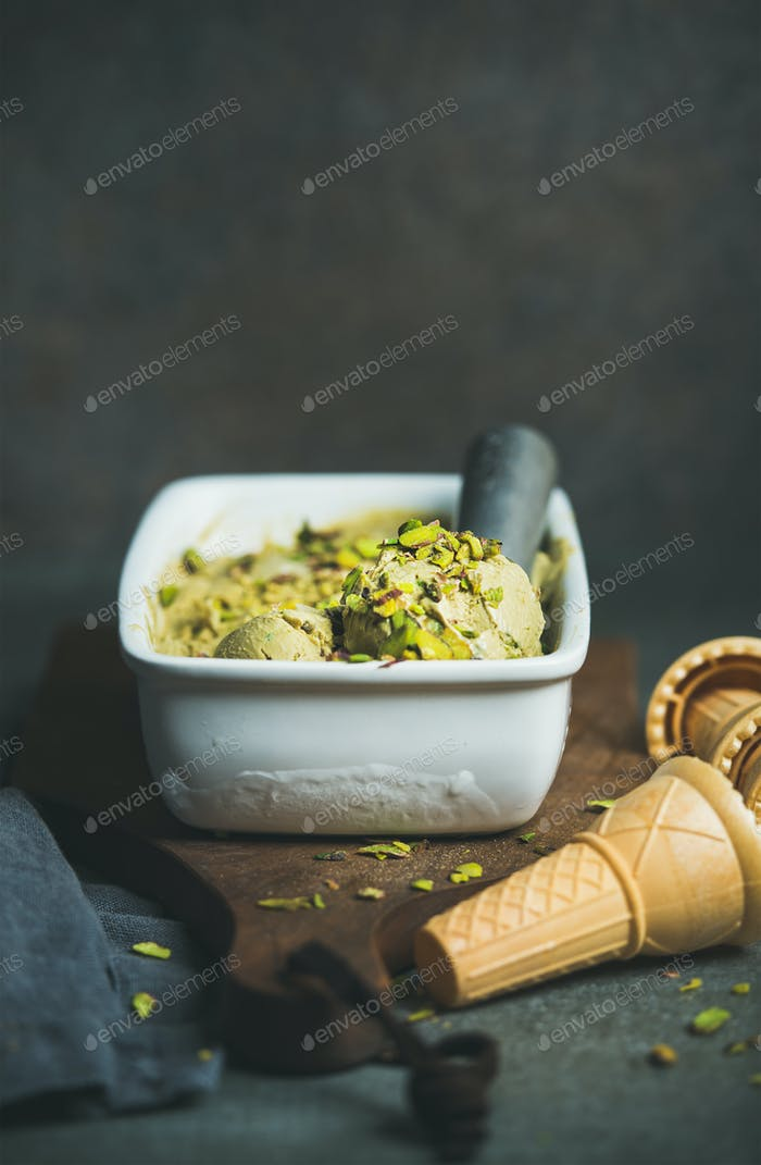 Homemade pistachio ice cream in ceramic mold with metal scooper