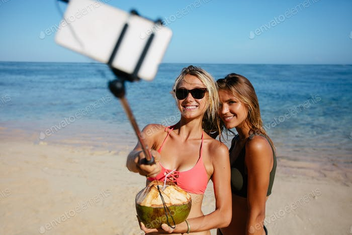 Happy friends taking pictures with selfie stick at the beach