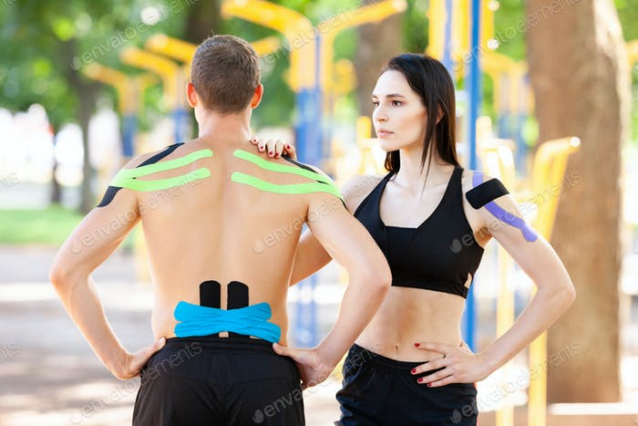 Athletes with kinesiological taping posing outdoors