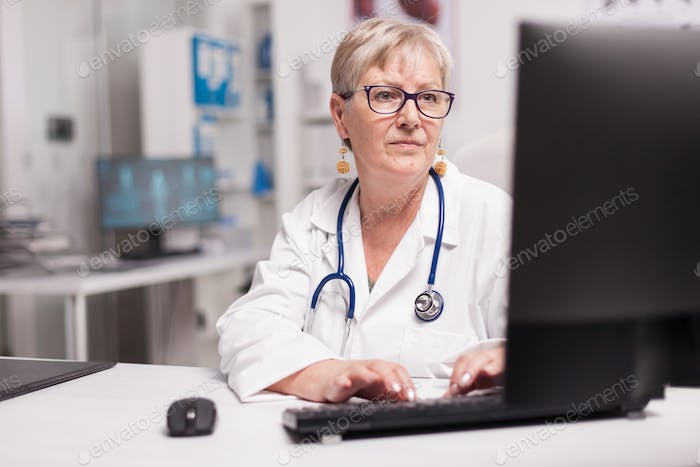 Mature doctor typing raport