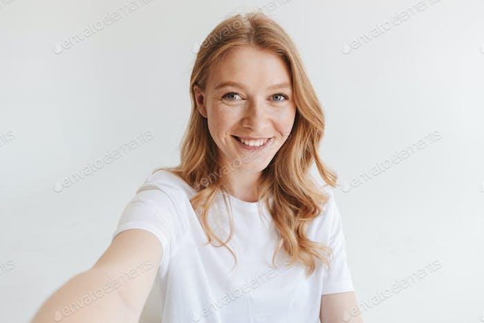 Happy redhead woman make selfie looking camera.