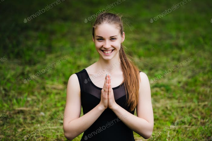 Young yoga teacher practicing outdoors in a park over green grass with copy space