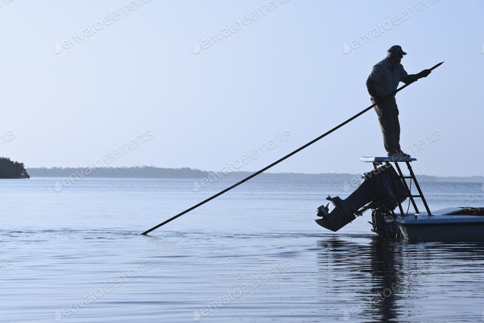 A fly fishing guide poling a flats skiff in search for tarpon and redfish along the coastline of