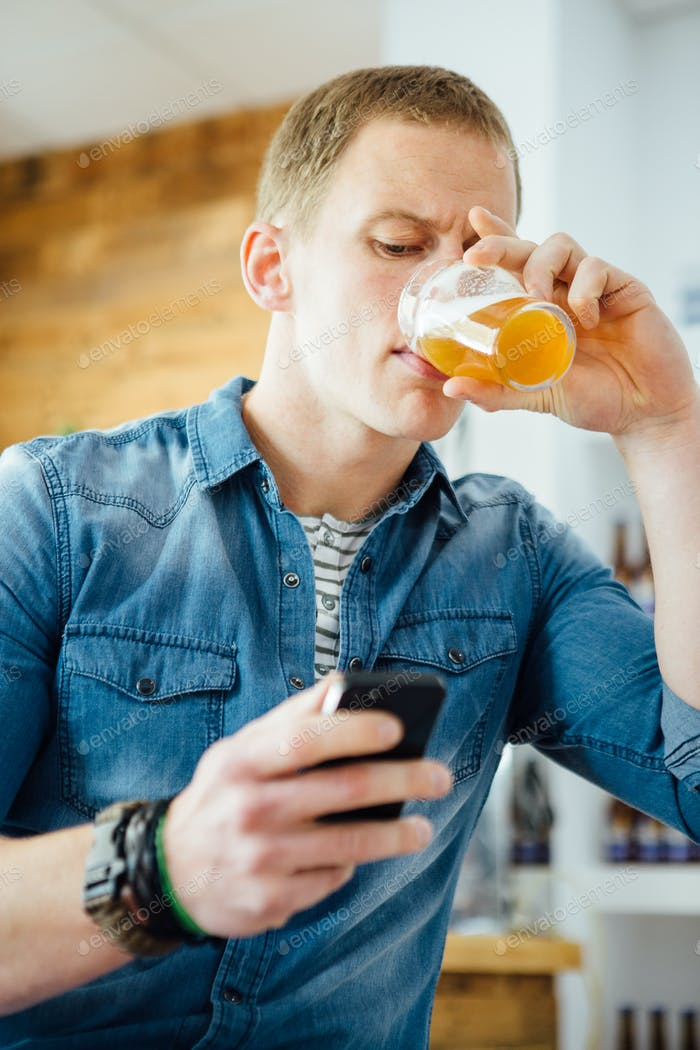 Man using phone while drinking beer
