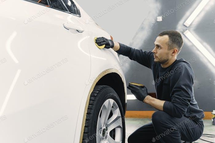Mann polieren ein Auto in einer Garage