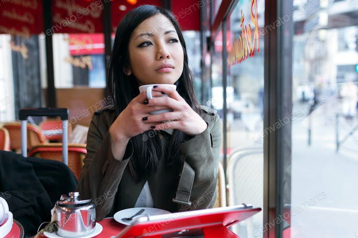 Thoughtful young asian woman drinking coffee in the terrace of a