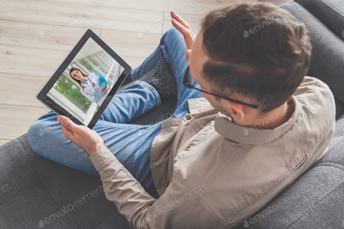 Man connects with doctor by pc tablet in the internet, while sitting at home