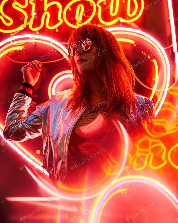 Sexy young beauty woman posing over night city dramatic red and yellow neon lights