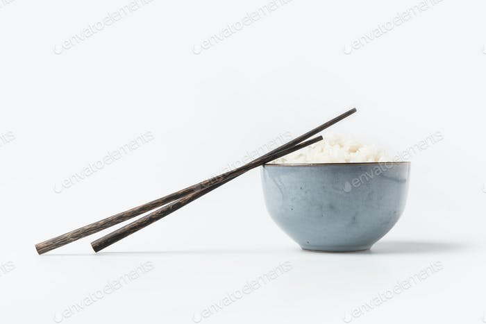 Schüssel mit leckerem Reis mit Stäbchen auf weißem Tisch
