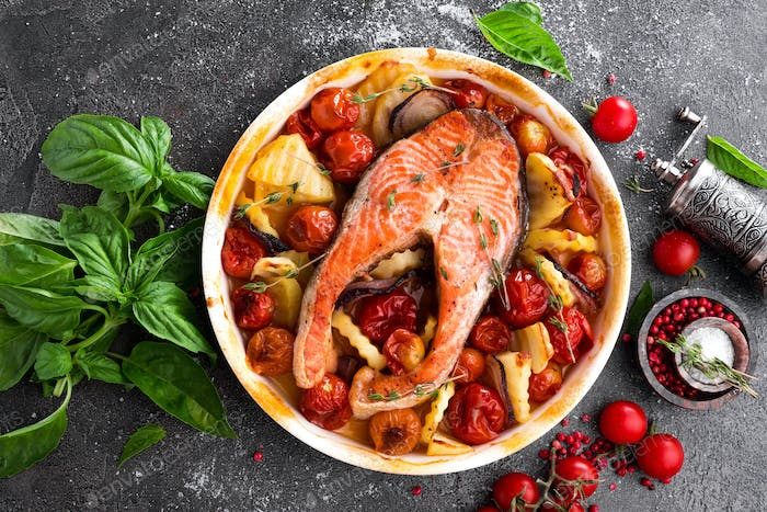 Grilled salmon fish steak with potato, onion and tomatoes. Baked salmon fish steak  with vegetables