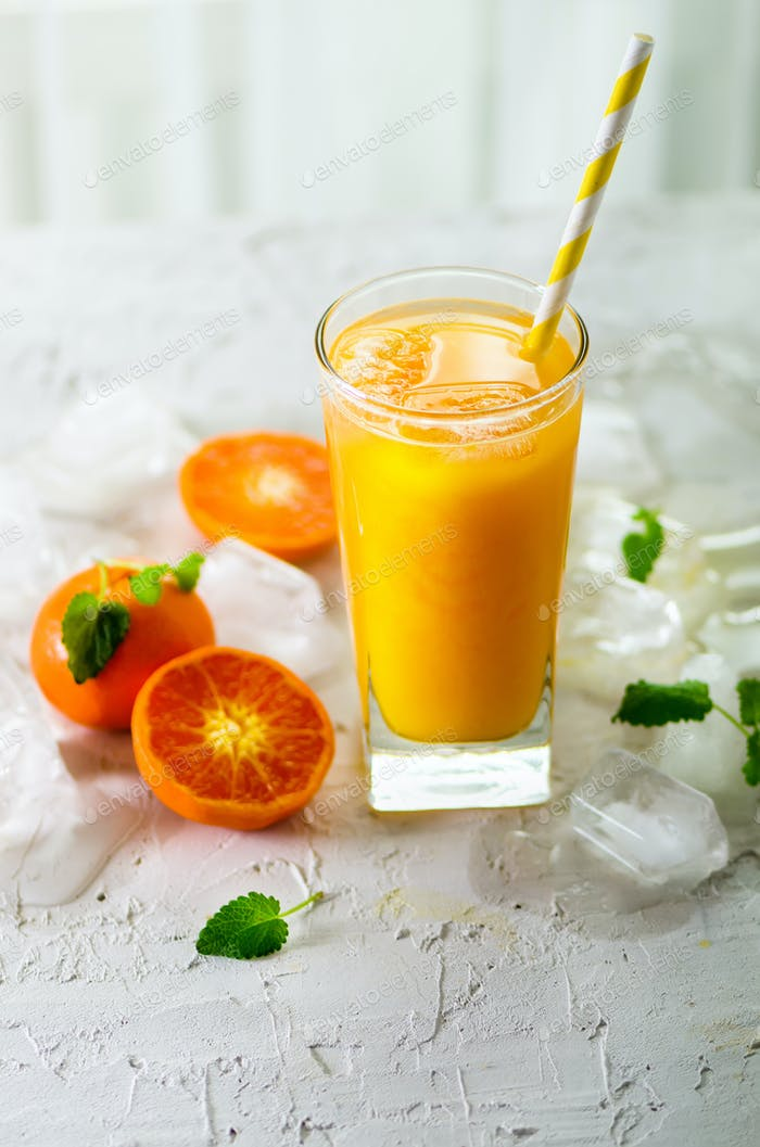 Orange juice with ice and tangerines on white background. Free space for your text. Copyspace. Cold