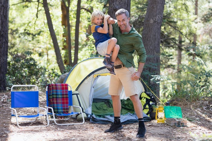 Playful father carrying son by tent at campsite