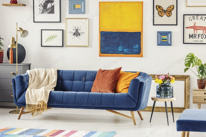Real photo of a navy blue couch with a blanket and orange pillow