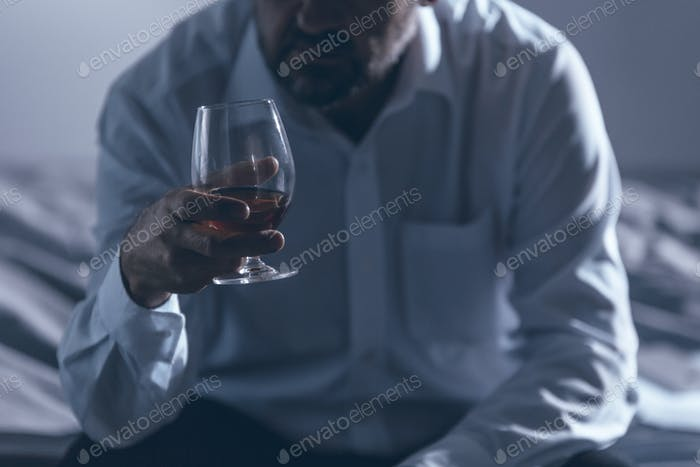 Lonely businessman drinking alcohol