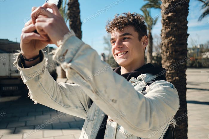 Portrait of attractive guy joyfully taking photo on smartphone outdoor