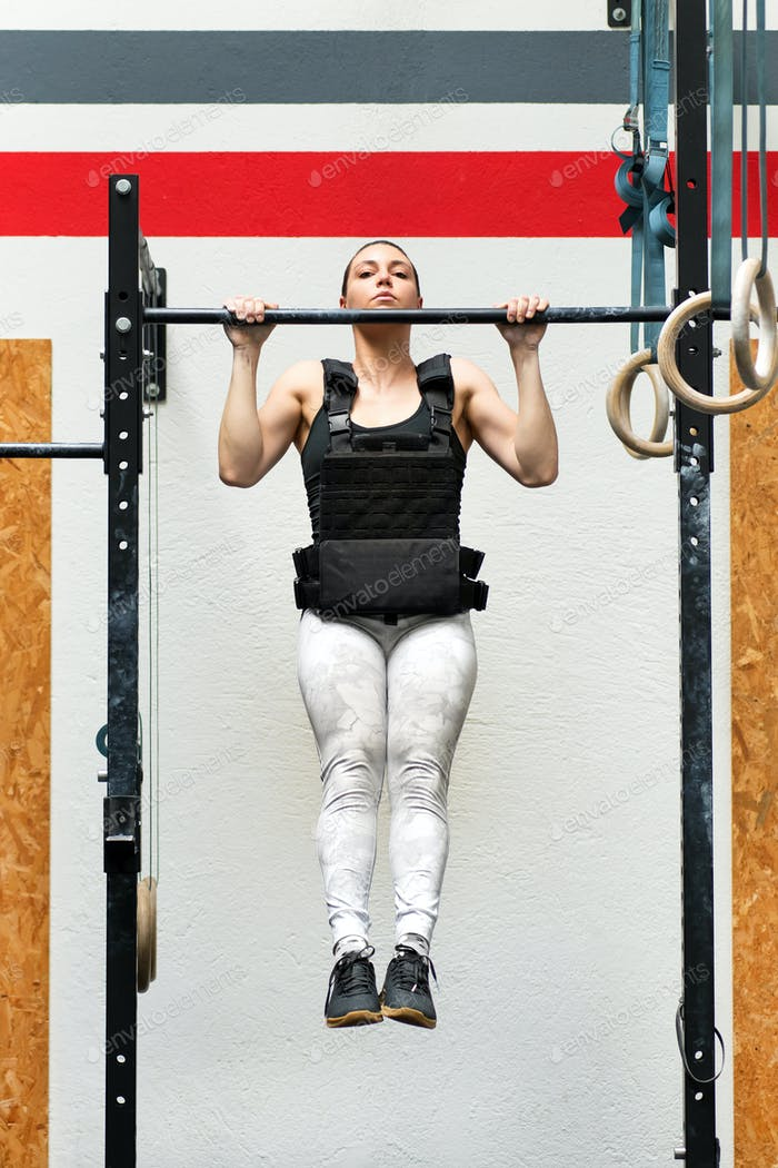 Athlete doing weighted pull-ups on a bar
