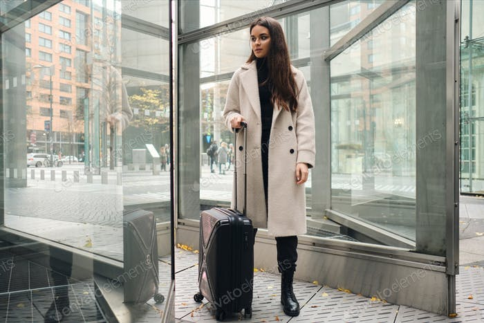Young stylish businesswoman in coat thoughtfully standing with suitcase