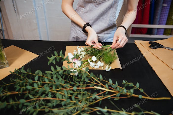Hands of young woman florist making bouquet with white flowers