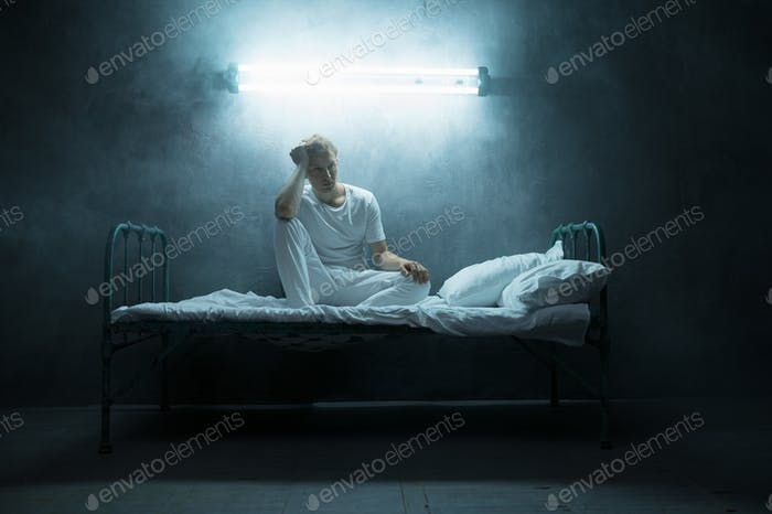 Psycho man sitting in bed, dark room on background