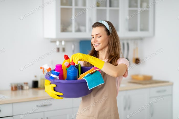 Portrait of positive young maid holding cleaning supplies at kitchen