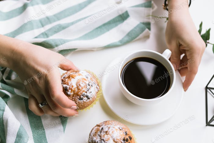 A cup of coffee in the hands and muffins on a white background and muffins