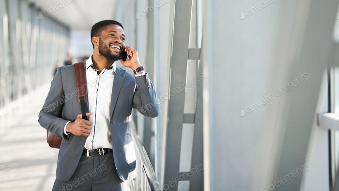 Happy Black Businessman Talking On Cellphone Walking Through Airport, Panorama