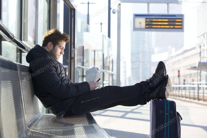 Man relaxing by train station platform with bag and mobile phone