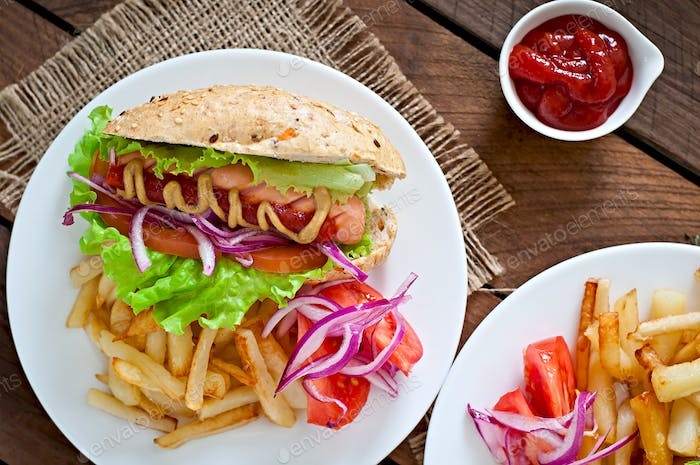Hot Dogs with French fries on white plate, close-up.