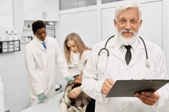 Confident vet doctor posing in clinic, looking at camera