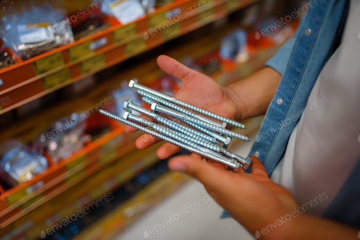 Consumer choosing tapping screws in hardware store