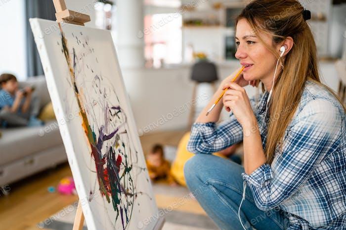 Glückliche junge Frau malt auf Leinwand zu Hause