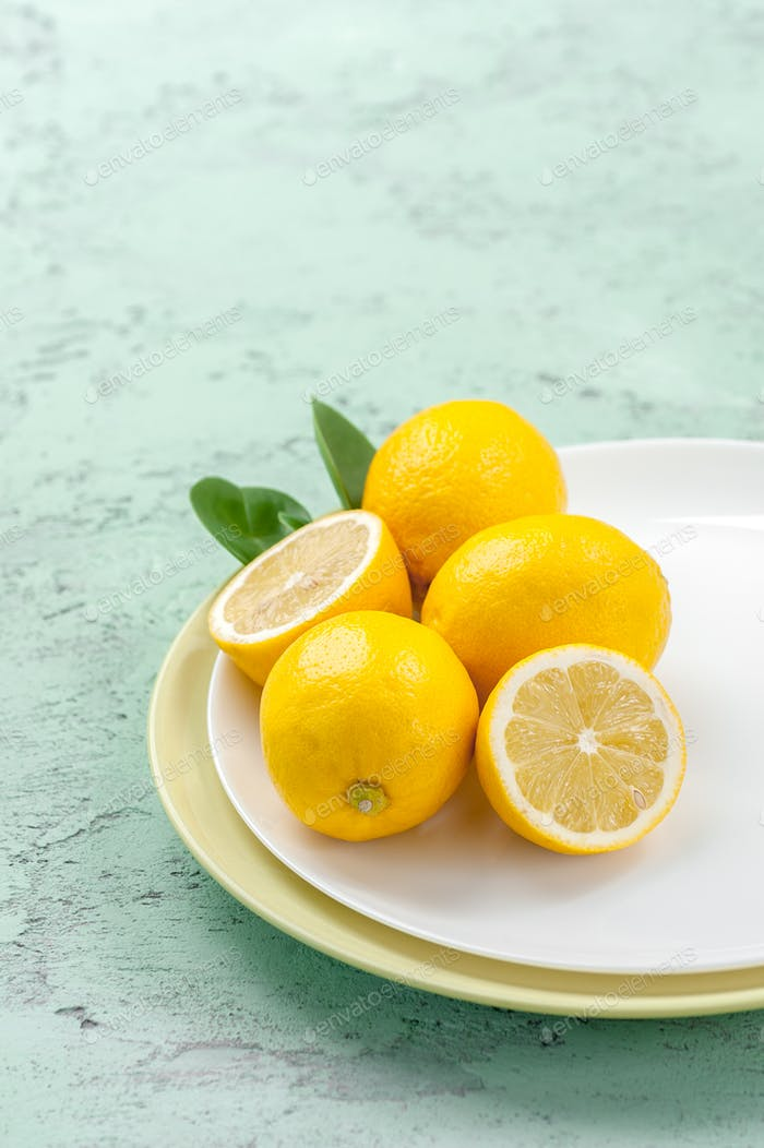 Ripe lemons on a plate on a mint-colored table.