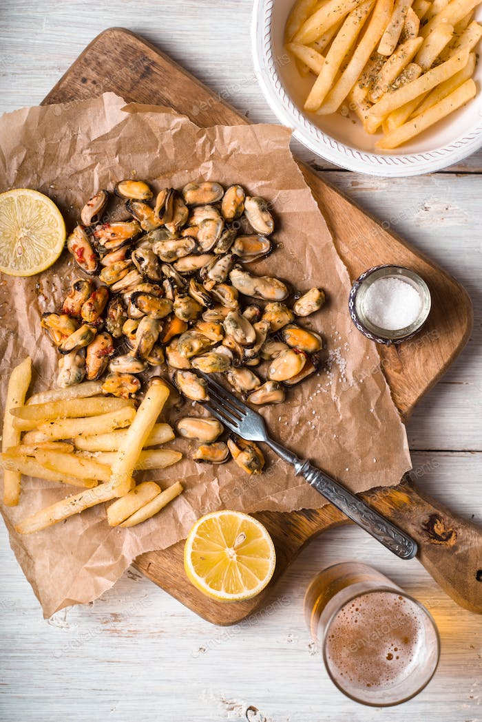 Mussels with lemons and French fries on the white wooden table vertical