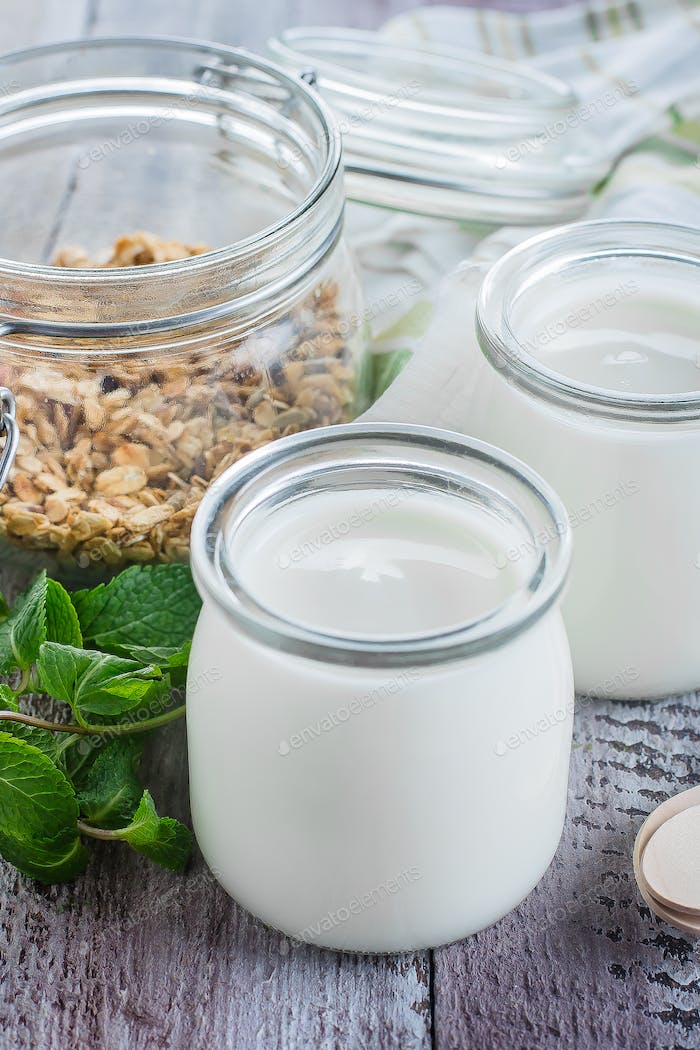 Two glass jar with greek yogurt and jar with homemade oat granola for healthy breakfast