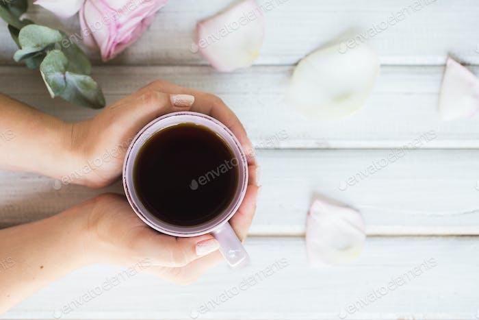 Frau hält heiße Tasse Tee auf einem hölzernen Hintergrund. Morgen, trinken, Pause