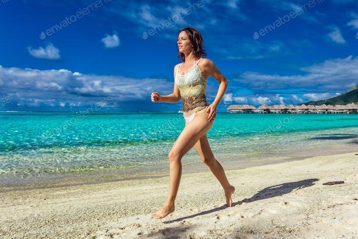 Junge lächelnde Frau mit Spaß am tropischen Strand