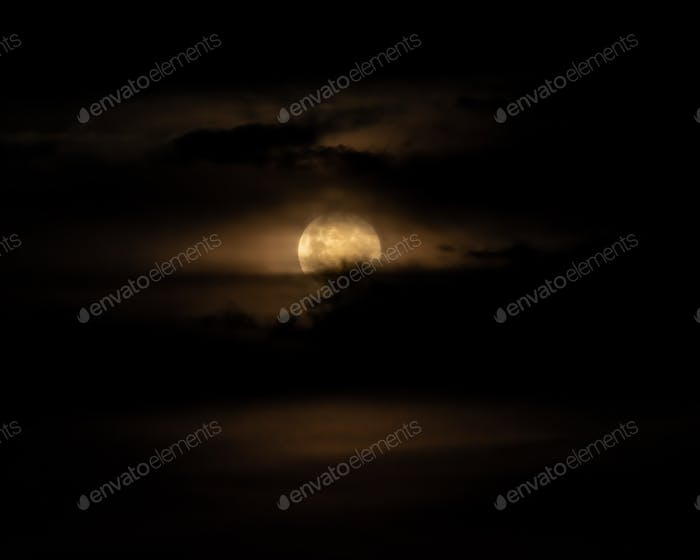 Full Moon Behind Clouds on Black Sky. Dramatic Sky. Horror Sky. Serenity Nature Background.