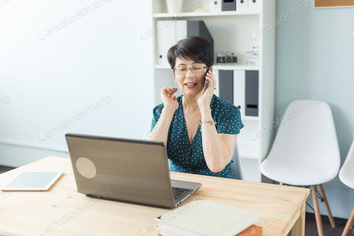 Office and business people concept - Middle aged woman at office working with laptop and making a