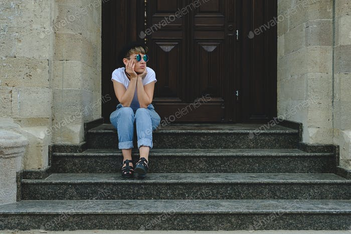Beautiful young hipster woman posing sitting on stairs