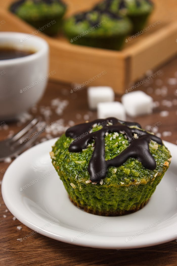Fresh muffins with spinach, desiccated coconut, chocolate glaze and cup of coffee