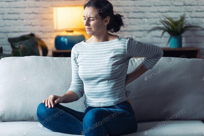 Junge Frau mit Rückenschmerzen sitzt auf dem Sofa im Wohnzimmer zu Hause.